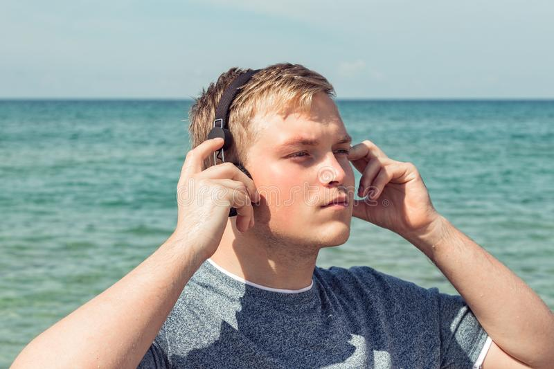 Portrait of a young man on the beach listening to music on headphones. Travel and relax. Portrait of a young man on the beach listening to music on headphones royalty free stock image