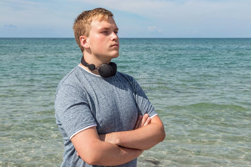 Portrait of a young man on the beach listening to music on headphones. Travel and relax. Portrait of a young man on the beach listening to music on headphones stock photos