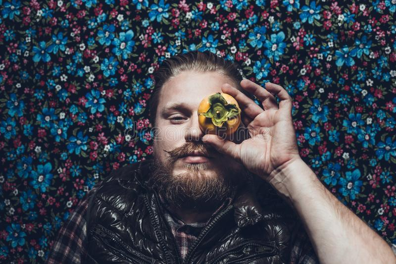 Young Man With Beard With The Persimmon On Colorful Background. Creativity Concept royalty free stock photos