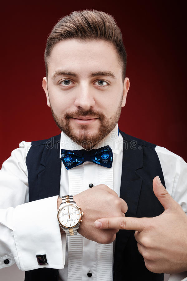 Portrait of young man with beard shows to watch on dark backgro. Portrait of young handsome man with a beard shows to watch on a dark background. punctuality stock photography