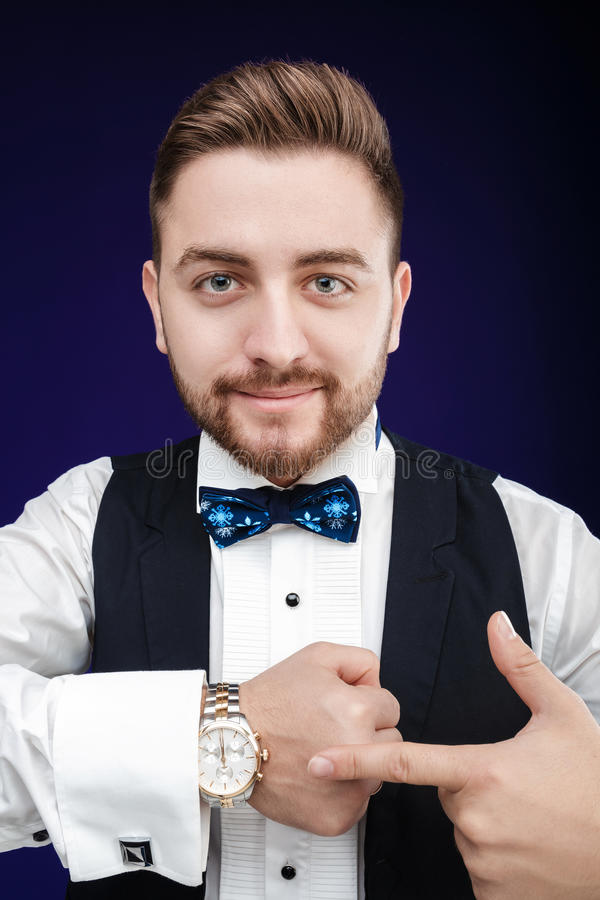 Portrait of young man with beard shows to watch on dark backgro. Portrait of young handsome man with a beard shows to watch on a dark background. punctuality royalty free stock images