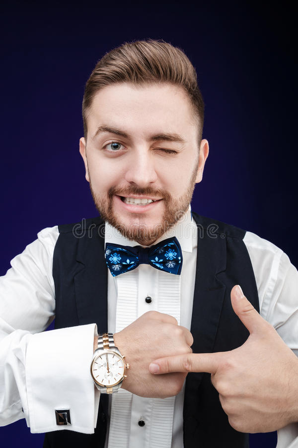 Portrait of young man with beard shows to watch on dark backgro. Portrait of young handsome man with a beard shows to watch on a dark background. punctuality royalty free stock image