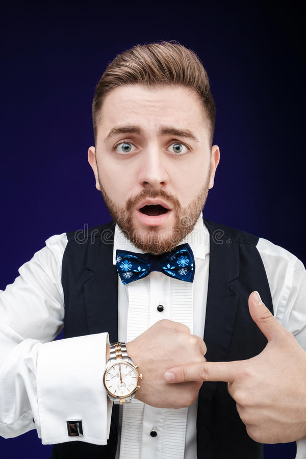 Portrait of young man with beard shows to watch on dark backgro. Portrait of young handsome man with a beard shows to watch on a dark background. punctuality royalty free stock photography