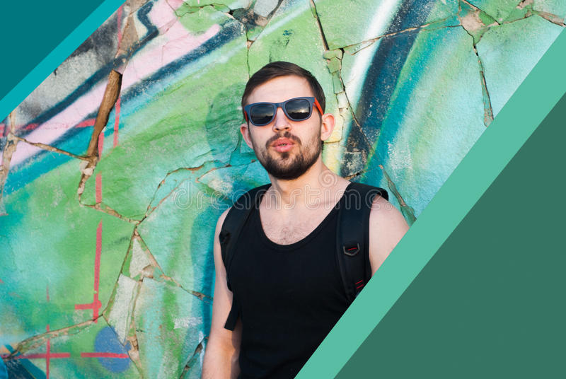 Portrait of a young man with a beard and sunglasses against graffiti background outdoors, sunset, stock images
