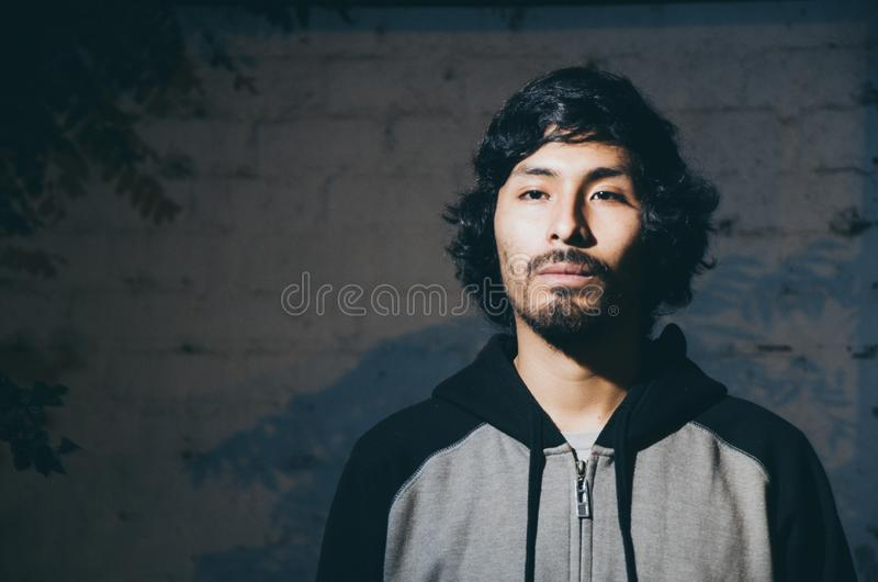 Portrait of young man with beard wearing shirt and with shadows of trees. Portrait of young man with beard wearing shirt and shades of trees in the park royalty free stock photos