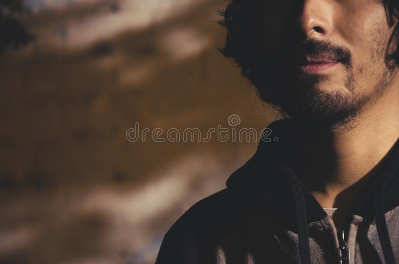 Portrait of young man with beard wearing shirt and with shadows of trees. Portrait of young man with beard wearing shirt and shades of trees in the park stock image