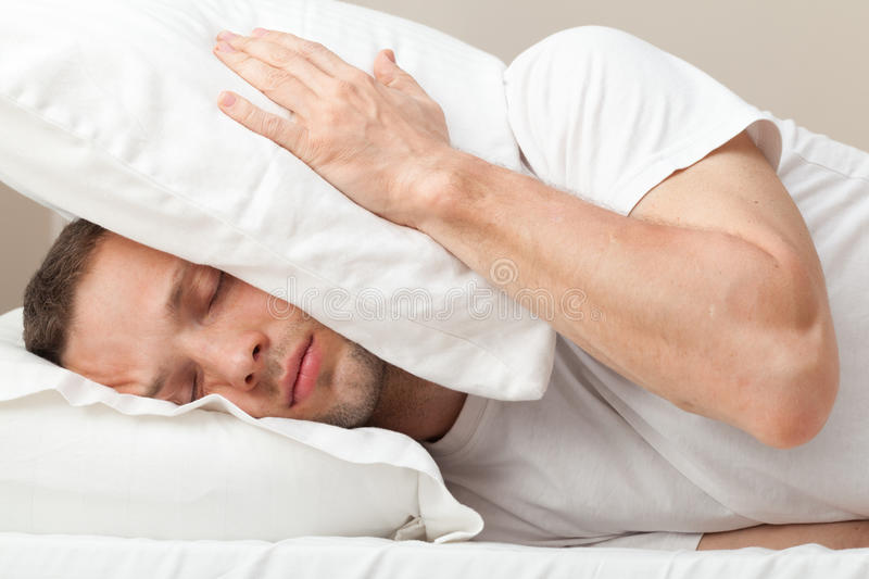 Portrait of Young man in bed hiding from noise stock photo