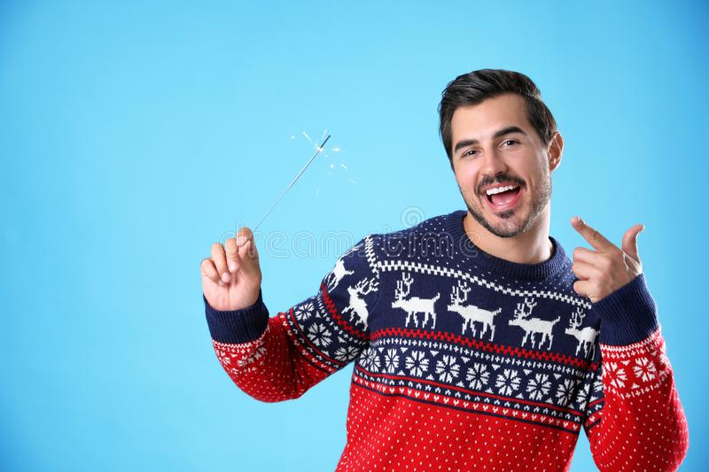 Portrait of young man in Christmas sweater with sparkler. On light blue background royalty free stock image