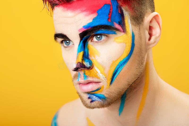 Portrait of young man with colored face paint on yellow background. Professional Makeup Fashion. fantasy art makeup stock photo