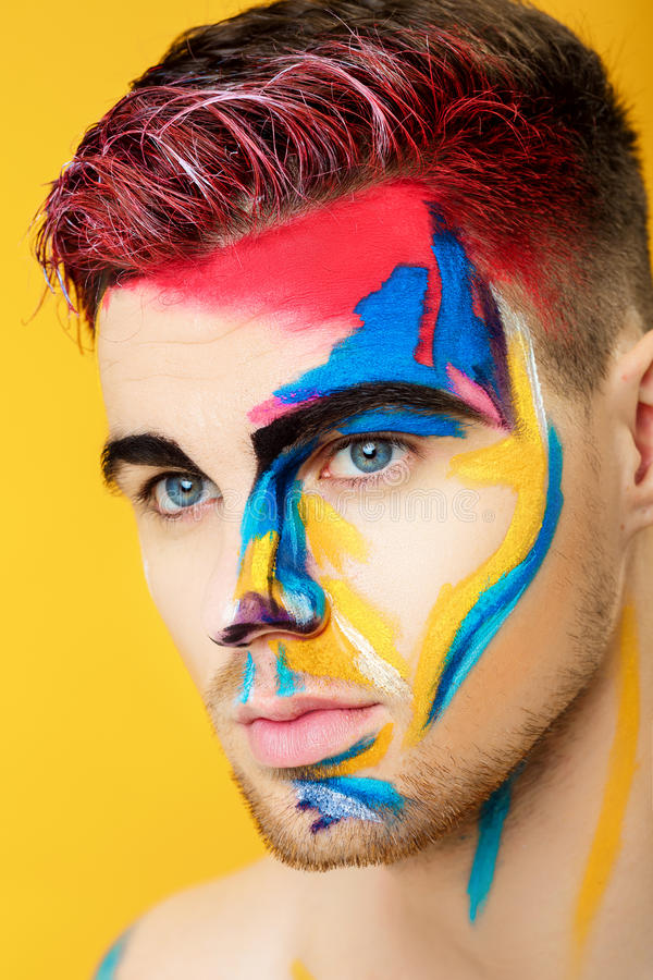 Portrait of young man with colored face paint on yellow background. Professional Makeup Fashion. fantasy art makeup royalty free stock photography
