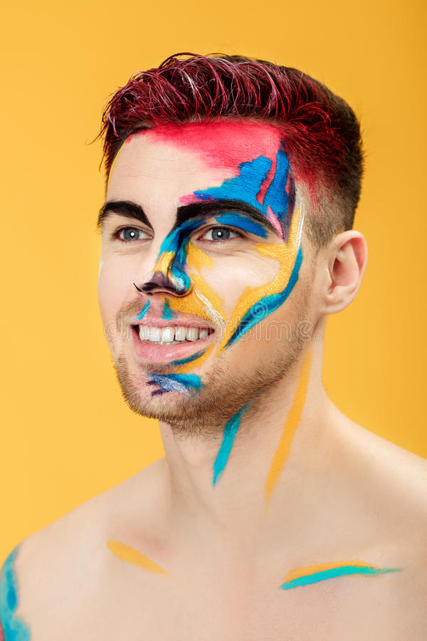 Portrait of young man with colored face paint on yellow background. Professional Makeup Fashion. fantasy art makeup royalty free stock photos