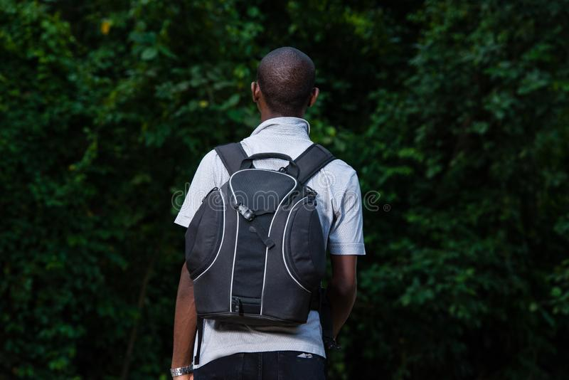 Portrait of young man in the countryside. Young man in black jeans backpack and goes to the forest royalty free stock photo