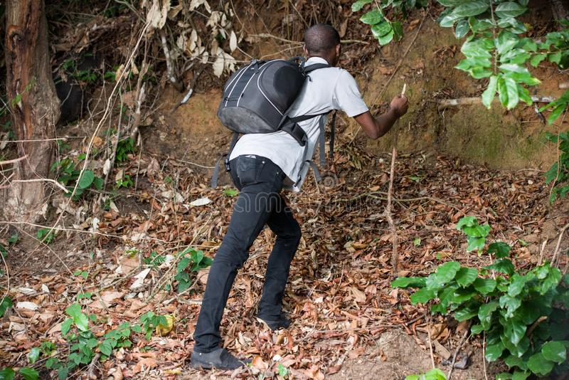 Portrait of young man in the countryside. Young man in black jeans with backpack going up hill royalty free stock image