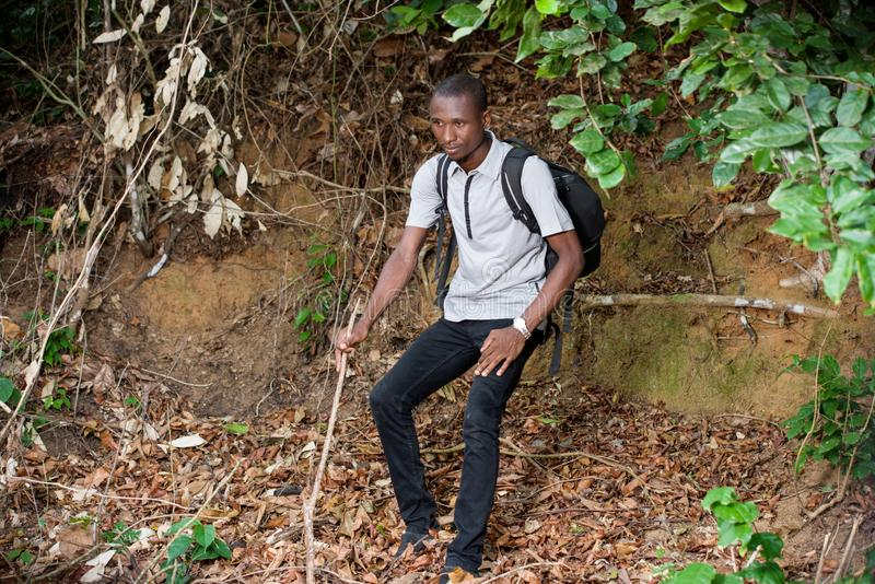 Portrait of young man in the countryside. Young man in black jeans with backpack sitting under foliage thinking stock photography