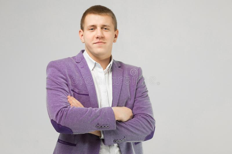 Young man in a jacket folded arms isolated on light background stock photo