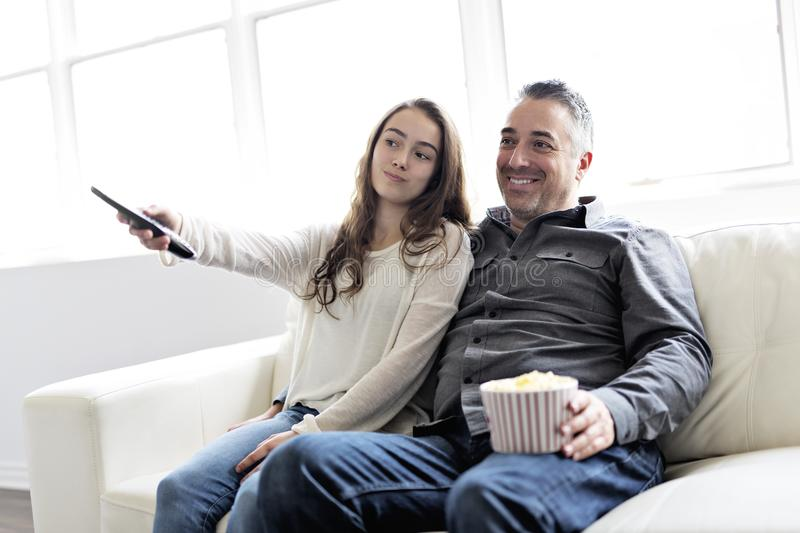 Portrait of a young man and daughter watching TV while eating popcorn on the sofa stock photo