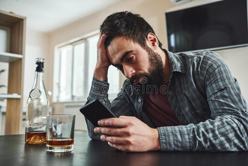If you can quit for a day, you can quit for a lifetime. Young man alcoholic, social problems concept, sitting, drinking stock photography