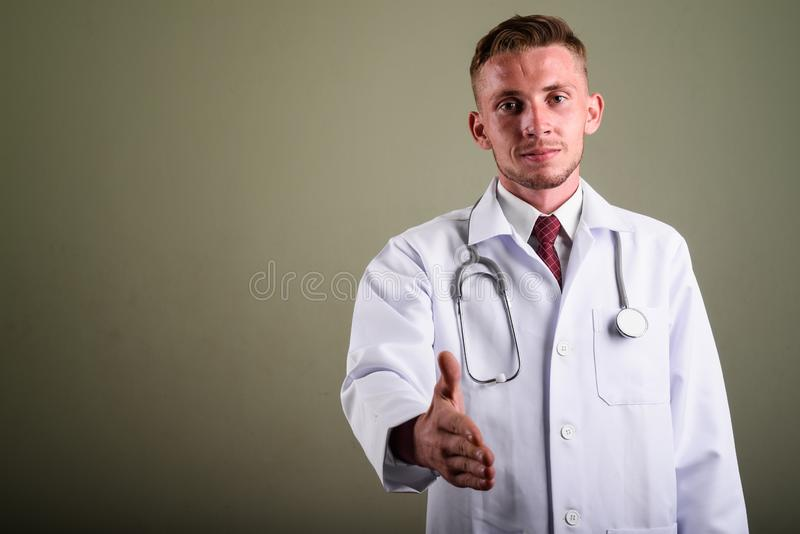 Portrait of young man doctor against colored background. Studio shot of young man doctor against colored background stock image