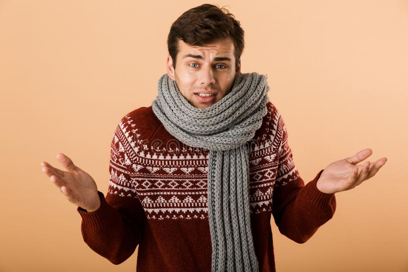 Portrait a young man dressed in sweater. And scarf isolated over beige background, shrugging shoulders royalty free stock photos
