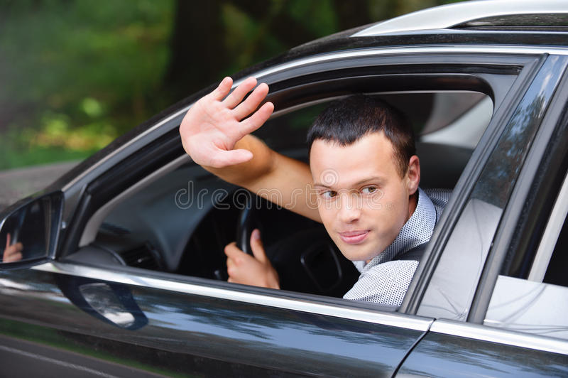 Portrait of young man driving car. Portrait of young attractive handsome brunette man driving car and greeting somebody with hand stock photography