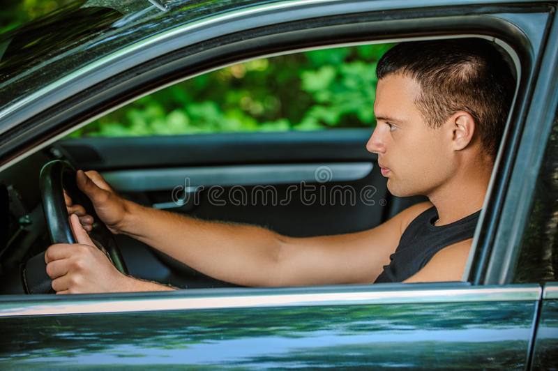 Portrait of young man driving car royalty free stock image