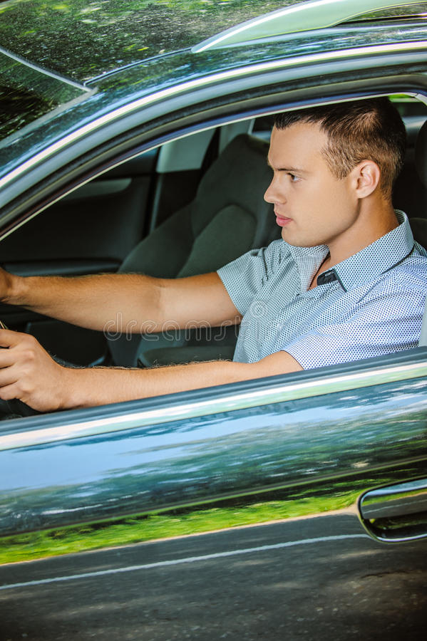 Portrait of young man driving car stock image