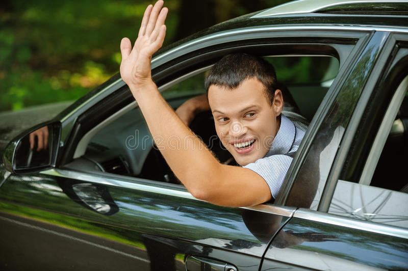 Portrait of young man driving car and greeting somebody with han royalty free stock photos