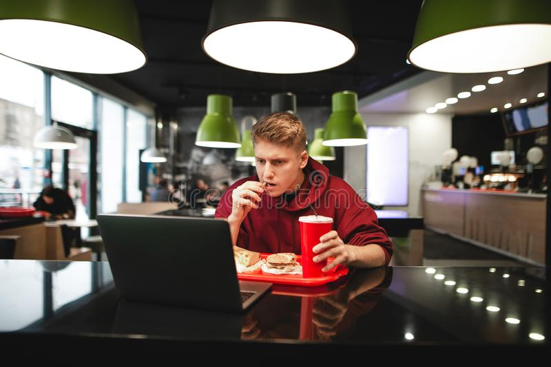 Portrait of a young man eating fast food at a restaurant and using a laptop stock image