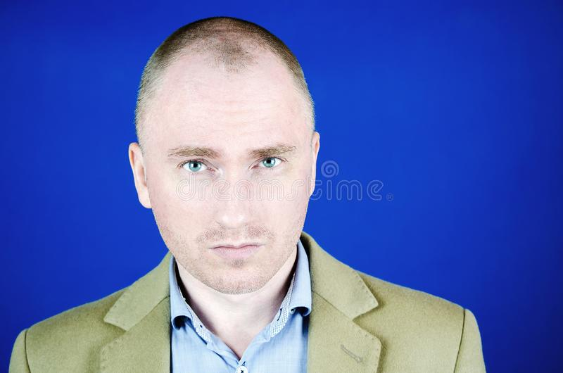 Portrait of a young man. The gaze of a handsome man in a cream coat with copy space. Blue background. Portrait of a young man. The gaze of a handsome man in a royalty free stock photography