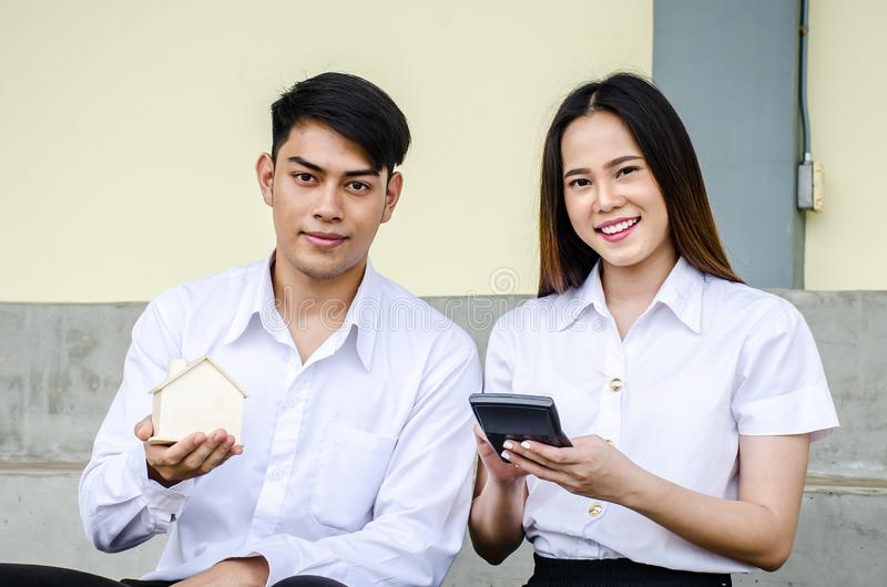 Portrait of young man and girl in university uniform sitting and hold a small house and calculator, Concept of sustaining a house stock photos