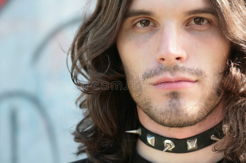 Portrait of the young man in gothic style. Close-up portrait of the young man in gothic style in dog-collar with thorn and with copy-space stock image