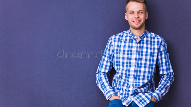 Portrait of young man smiling on gray background. Portrait of young man on gray background stock photo