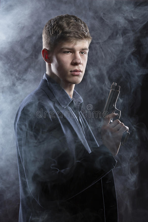 Portrait Of Young Man With Gun. Dark Background. royalty free stock images