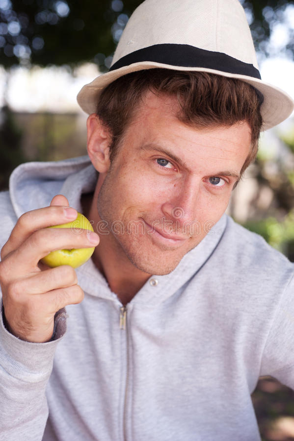 Portrait of a young man holding apple stock image