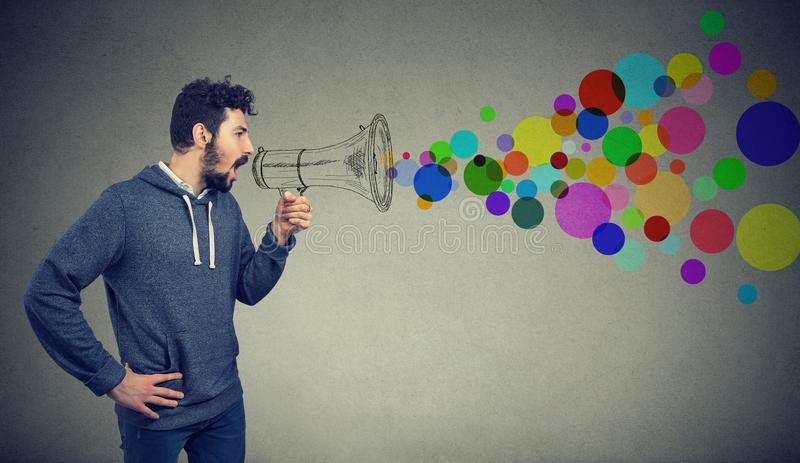 Young man holding screaming in megaphone making an announcement. Portrait young man holding screaming in megaphone isolated on gray background. Propaganda royalty free stock photos