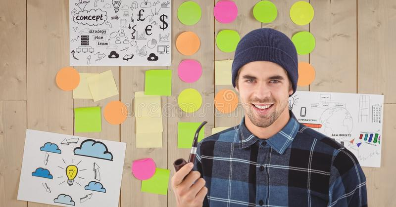 Portrait of young man holding tobacco pipe against sticky notes and drawings on wall. Digital composite of Portrait of young men holding tobacco pipe against stock photos