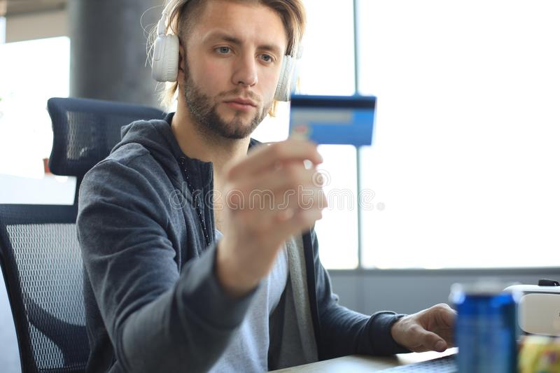 Portrait of a young man holds and using credit card for game money top up.  stock images