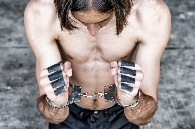 Portrait of young man kneeling on floor with handcuffs on hands royalty free stock image