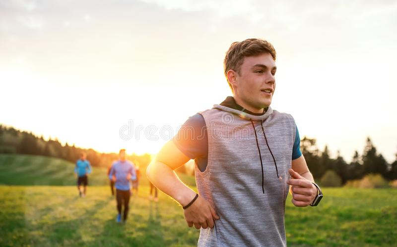 A portrait of young man with large group of people running in nature. royalty free stock photos
