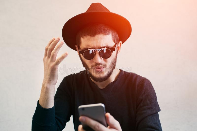 Portrait of young man looking shocked at smartphone, dressed in black, wearing sunglasses and hat, over white background.  royalty free stock photography
