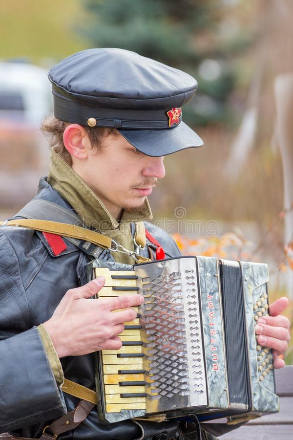 Portrait of a young man in a military uniform of the Red Army Commissioner during the civil war period with a harmonium in his ha. Russia Samara November 2018 royalty free stock photos