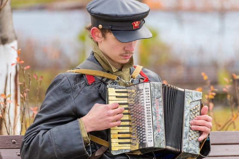 Portrait of a young man in a military uniform of the Red Army Commissioner during the civil war period with a harmonium in his han. Russia Samara November 2018 stock photos