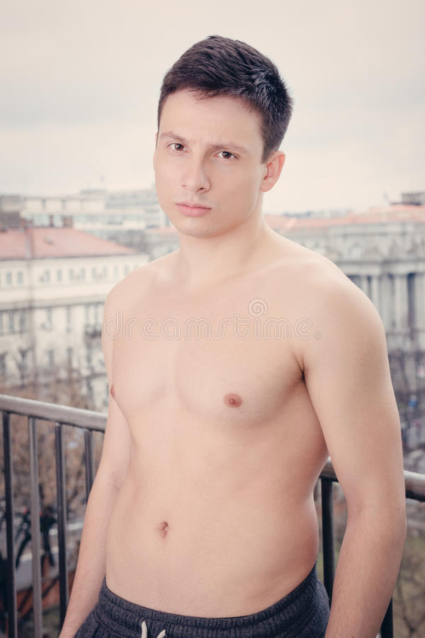 Portrait of young man with naked torso. Leaning on fence , Shirtless guy standing on terrace thinking stock photo