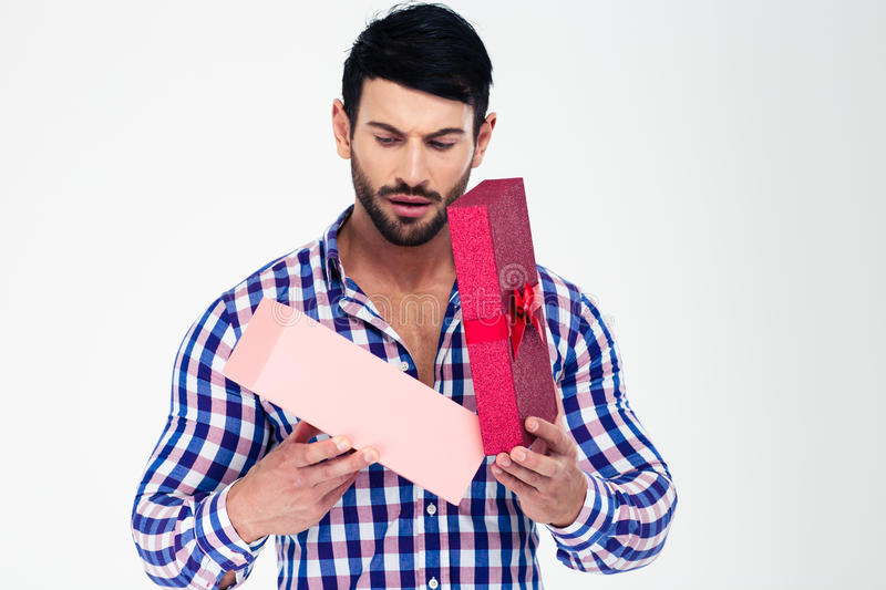 Portrait of a young man opening gift box. Isolated on a white background royalty free stock photo