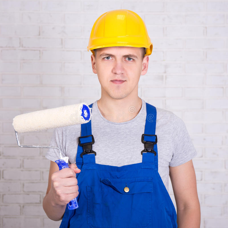 Portrait of young man painter in workwear with roller paintbrush royalty free stock photography