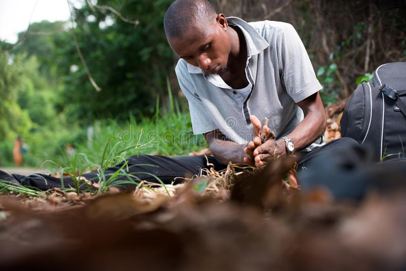 Portrait of young man in park. Young man in black jeans gray tee shirt sitting in park and plays with dead leaves stock photos