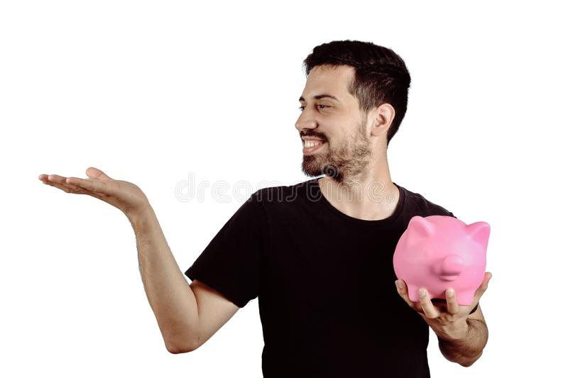 Young man with piggy bank. Portrait of young man with piggy bank and showing something on studio. Save money concept stock image