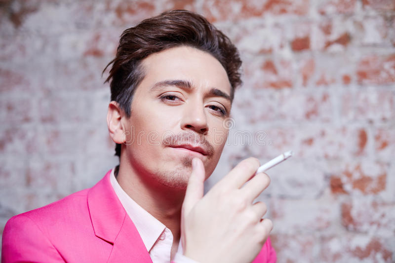 Portrait of young man in pink suit with cigarette royalty free stock photo