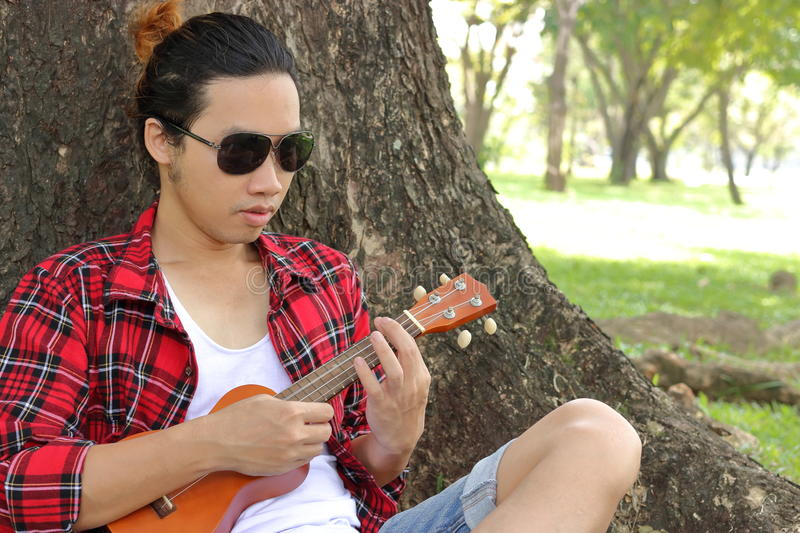 Portrait of young man playing ukulele in public outdoor park. royalty free stock image