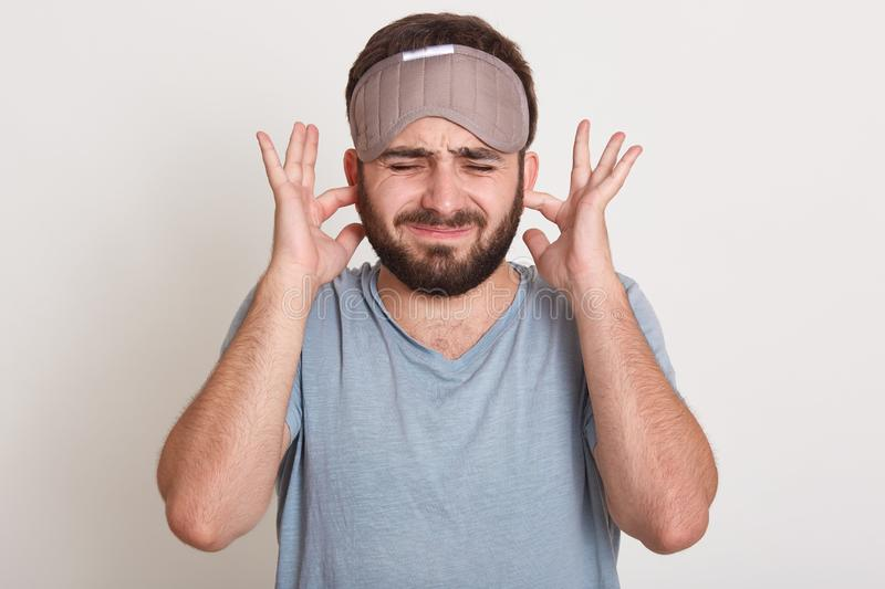 Portrait of young man plugging ears with index fingers and keeping eyes closed, guy covering his ears, studio shot isolated over stock images